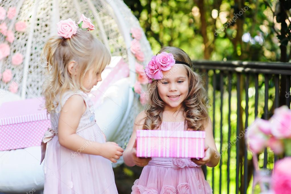 Child Giving Birthday Gift To Her Friend Stock Photo