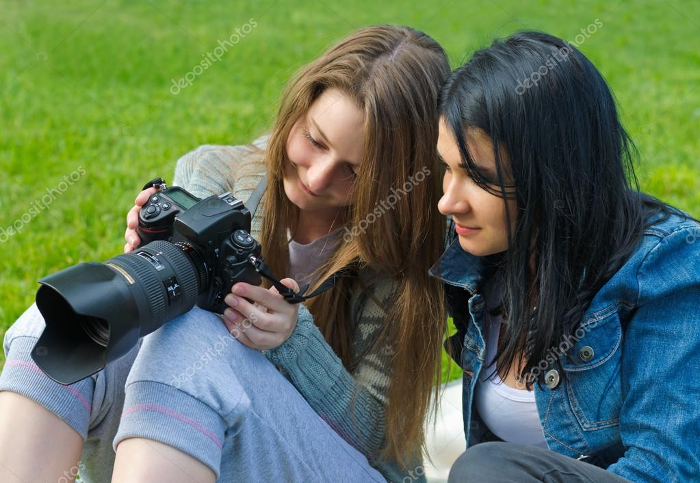 Women checking viewfinder of camera