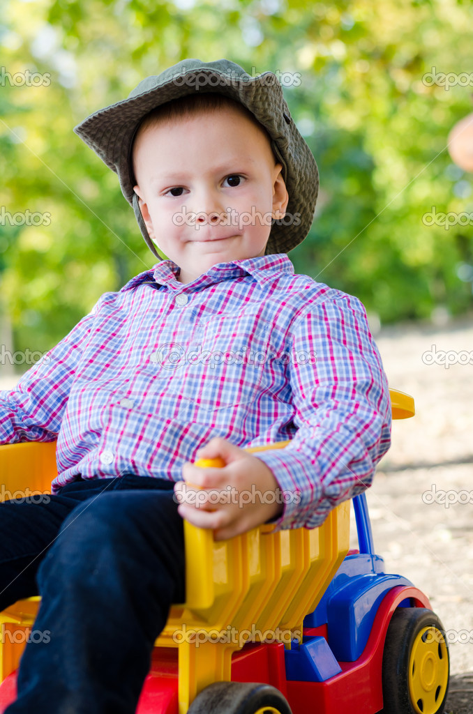 Little boy riding a toy truck