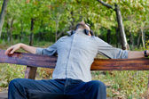 Photo Exhausted man relaxing on a bench