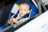 Little boy in a child safety seat sitting patiently in the back of a car