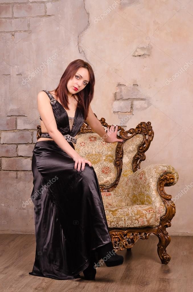 Young Woman Sitting On The Arm Of A Fancy Chair Stock