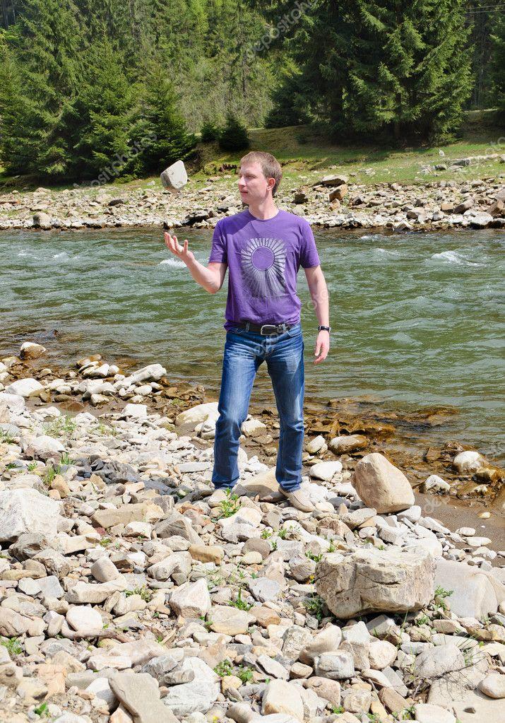 Man examining a riverbed rock
