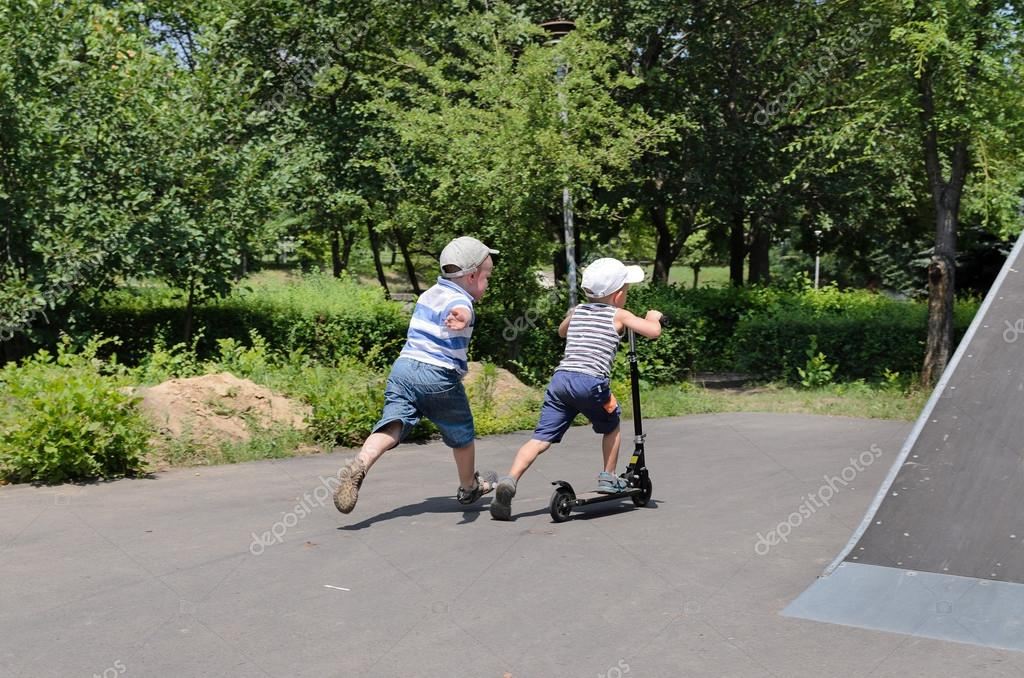 Two young boys playing with a scooter
