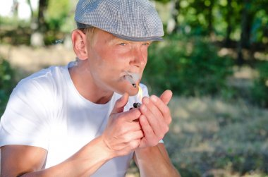 Man lighting up a home made cigarette