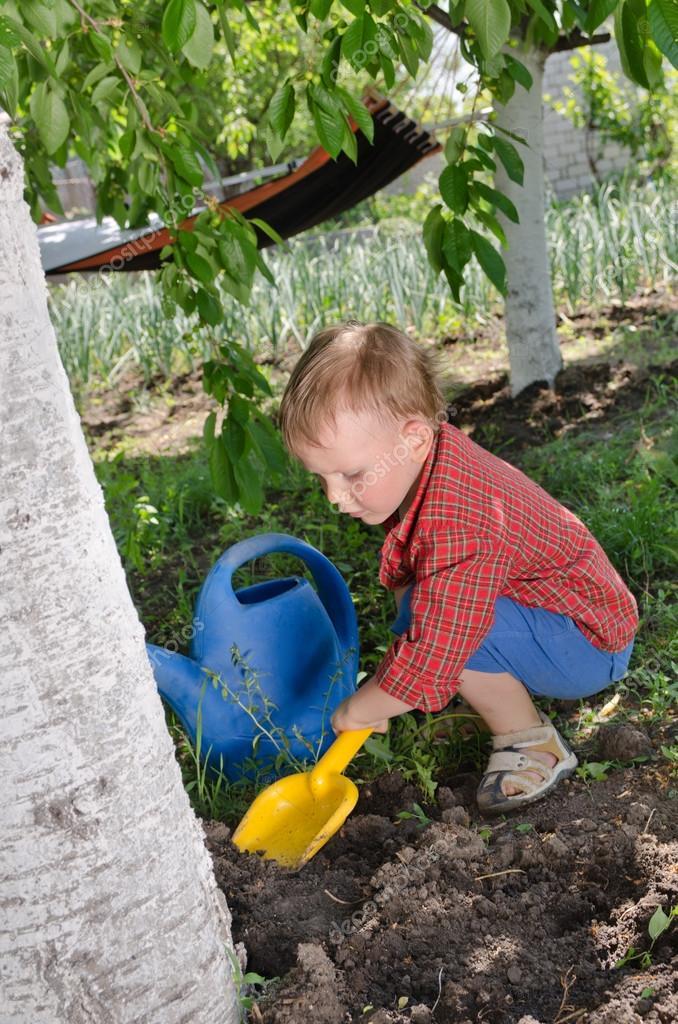 Cute little boy digging in the garden