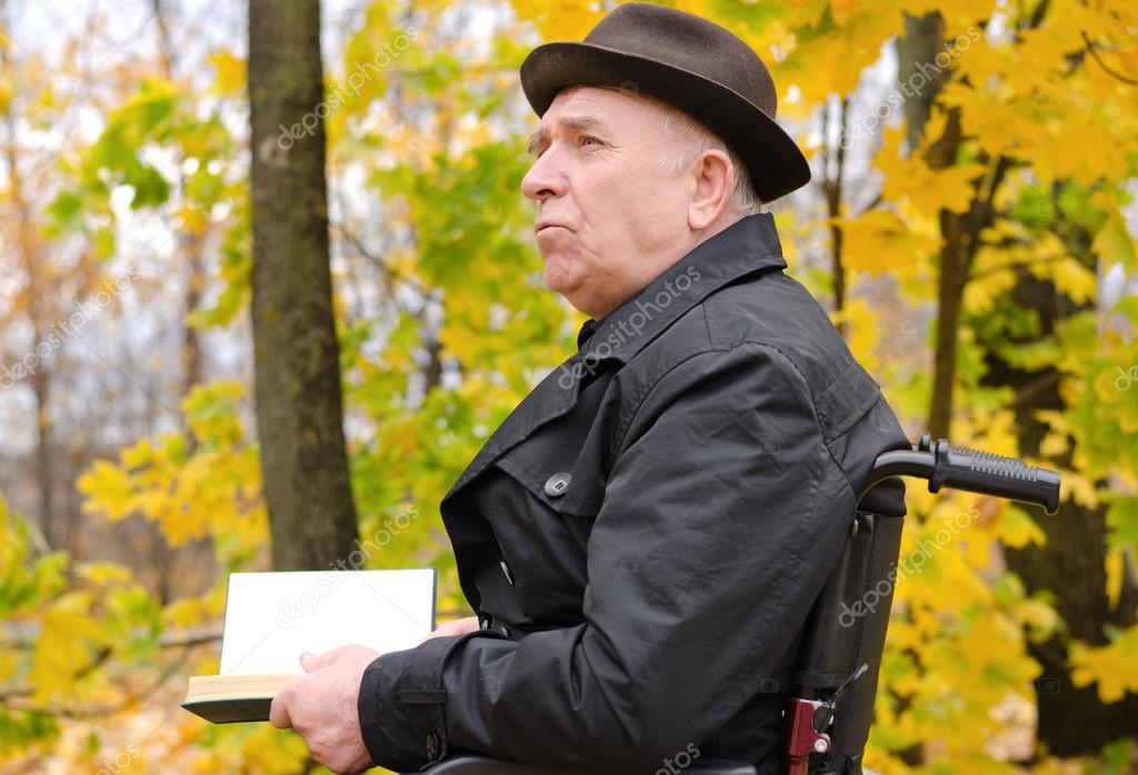 Pensive man reading on park in autumn