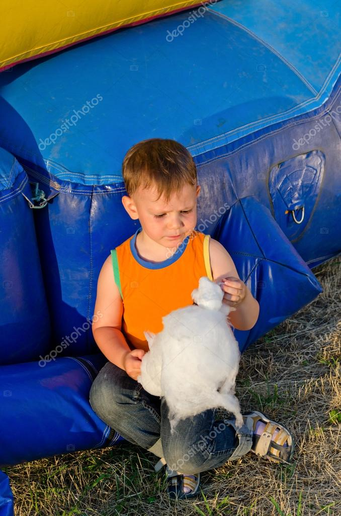 Small boy eating a portion of candy floss
