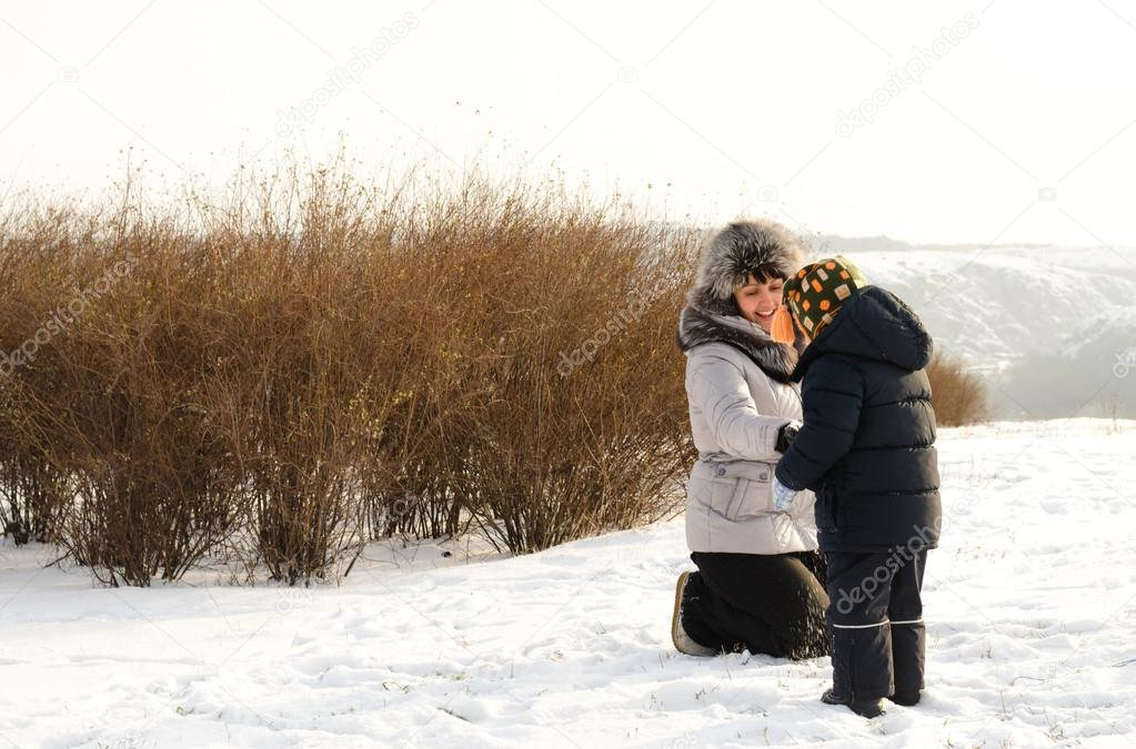 Caring mother checking her sons clothing in winter