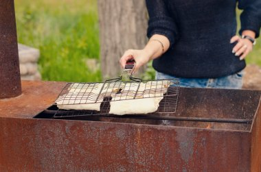Woman preparing kebabs to grill on a BBQ