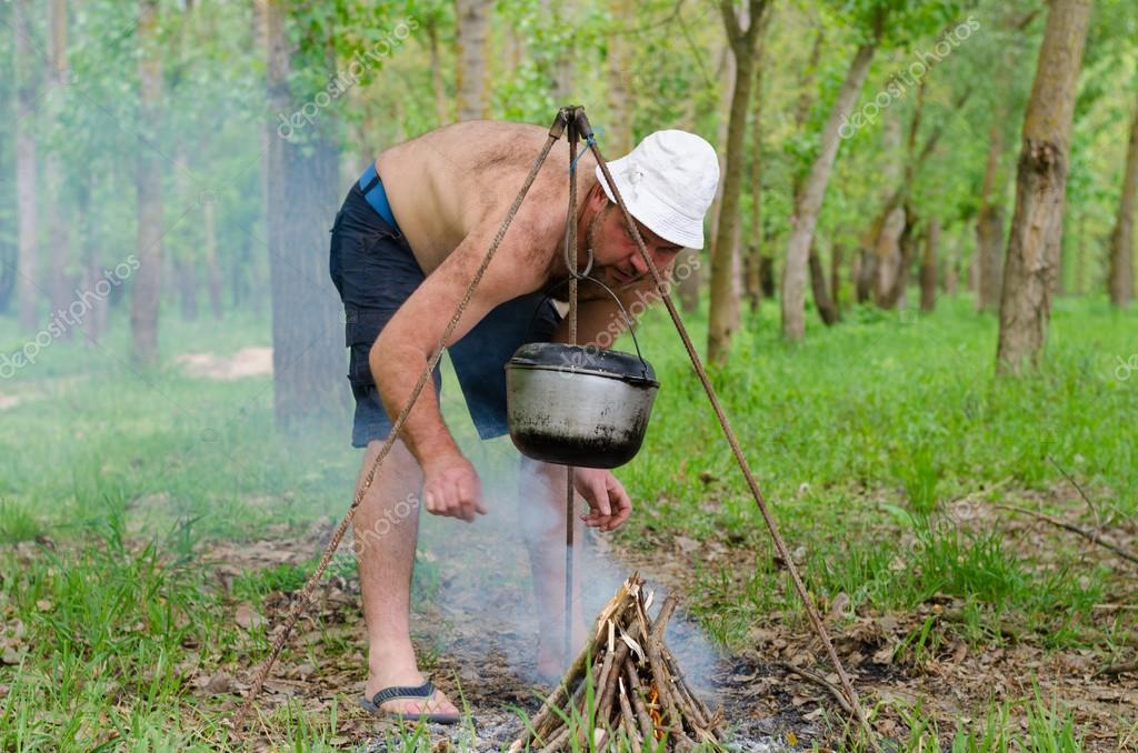 Man starting a cooking fire in a campsite