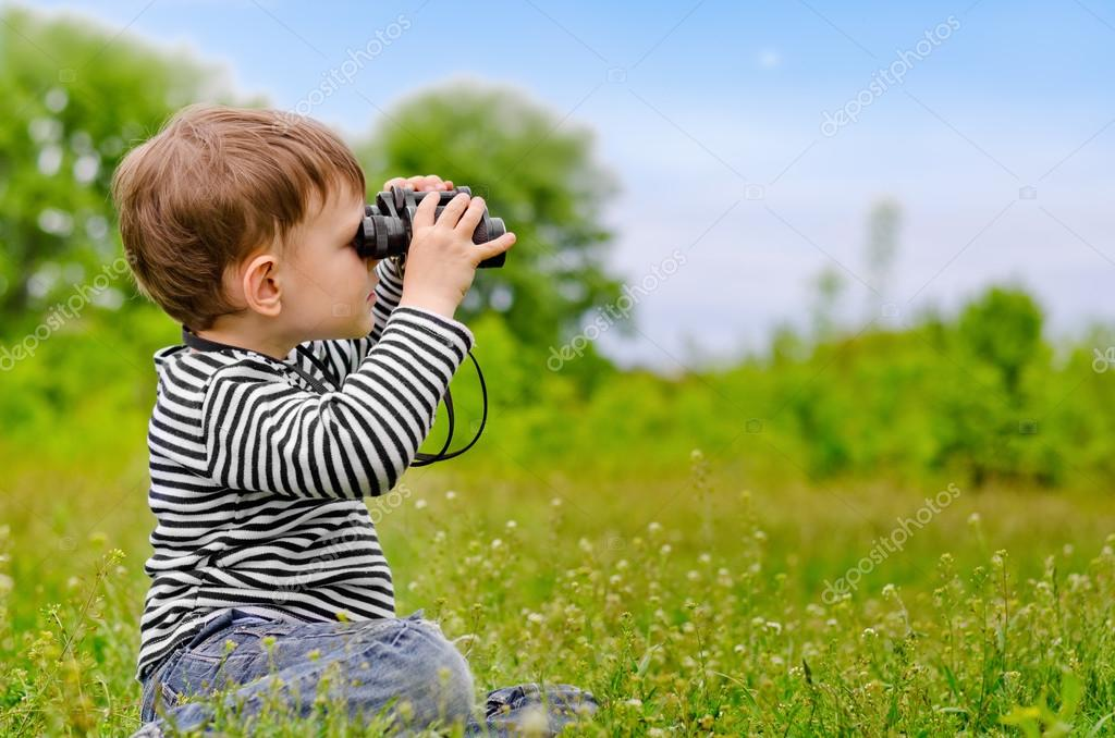 Little boy looking at the camera with binoculars