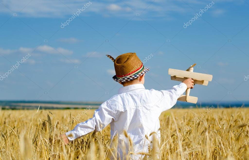 Cute little boy flying a toy plane in a wheatfield