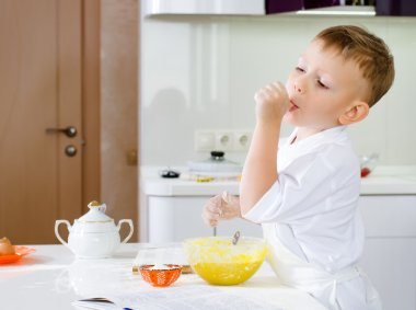 Cut little chef tasting his batter mixture