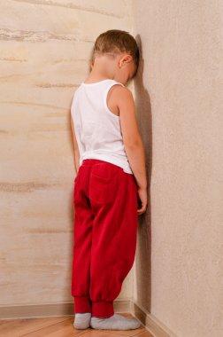 Little boy standing in a corner sulking