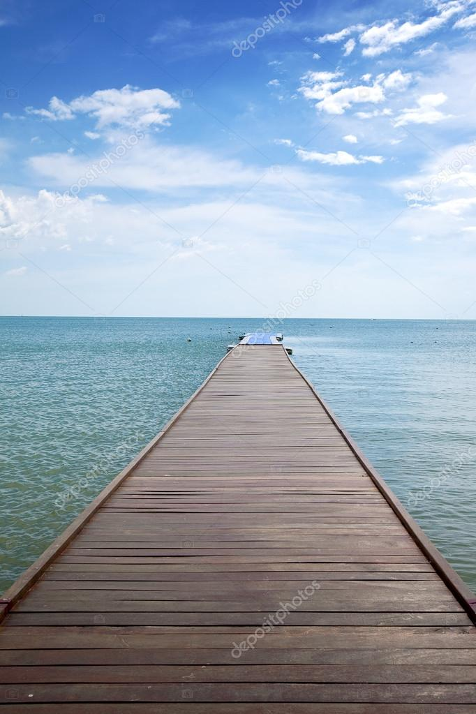 Wooden boardwalk above water out towards open ocean