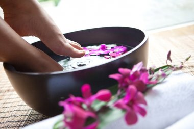 Feminine feet in orchid spa bowl