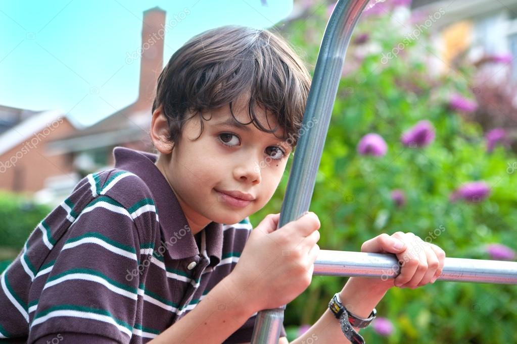 hermoso joven en un marco de escalada en el jardín — Foto de stock ...