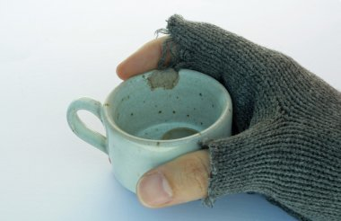hand of a poor man holding a cup of coffee with coins