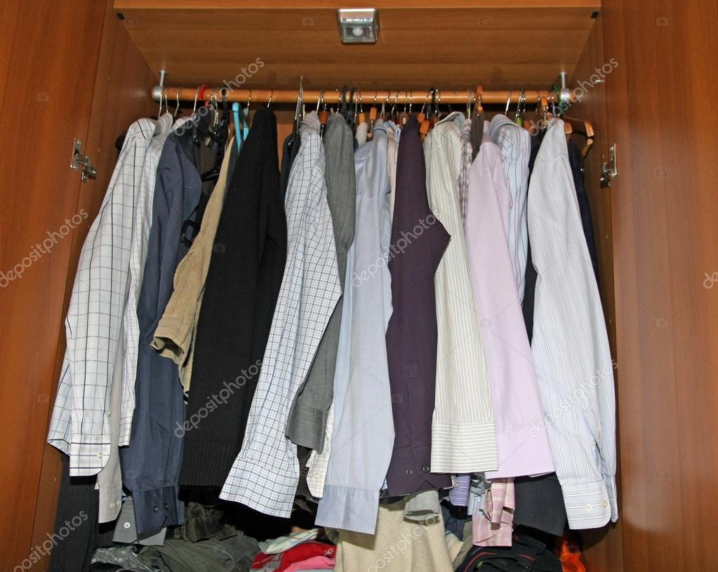 en el interior de un armario lleno de camisas de vestir y sweaters para hombre u