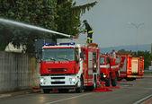 Hasiči s hasičský vůz při zhasínání ohně