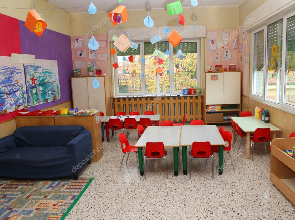 Nice classroom in a kindergarten with tables and little chairs