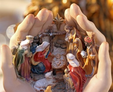 hand holding the crib with statuettes of the Nativity
