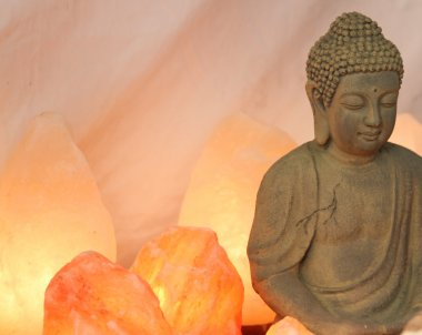 statuette of Buddha in prayer with salt lamps lit during the med