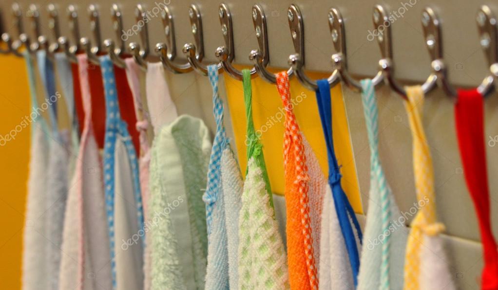 handdoeken hing op metalen haken in de badkamer van een kleuterschool stockfoto