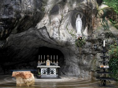 Statue of the Virgin Mary in the grotto of Lourdes attracts many