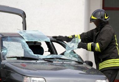 Fireman while breaking a car windshield to release the people in
