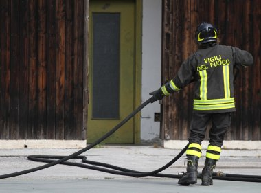 italian fireman collects the water hose after turning off the fi