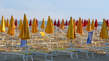 closed umbrellas and deckchairs on the beach at sunset on the se