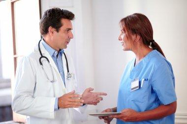 Handsome hispanic doctor talking with lady nurse