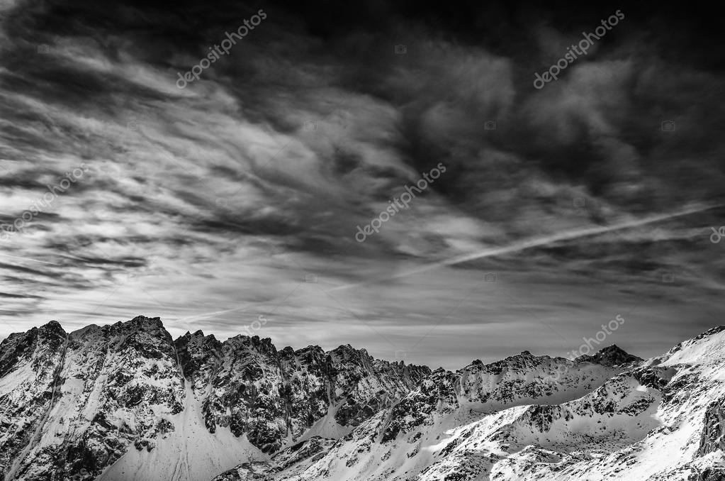 Winter mountains landscape with blue cloudy sky