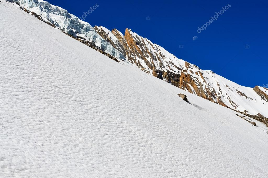 Snow mountain slope with rocks, glacier and blue sky with moon