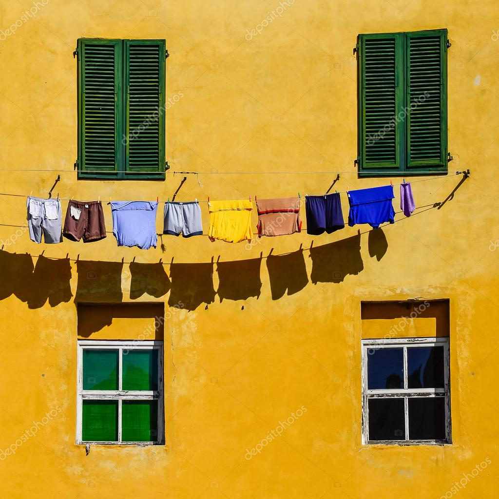 Detail of colorful yellow house walls, windows and clothes — Stock ...