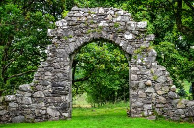 Old stone entrance wall in green garden
