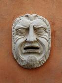 starověké masku na stěně budovy