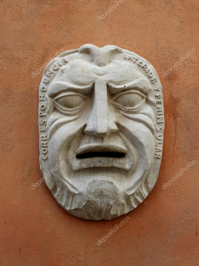 Ancient mask on the wall of the building