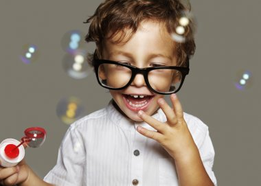 Little boy with glasses and soap bubbles