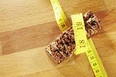 Photo Chocolate muesli bar measuring tape on wooden background