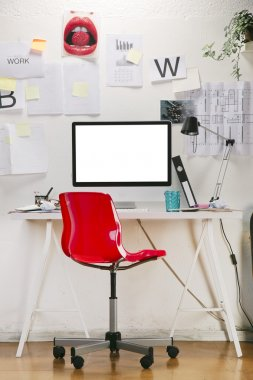 Modern creative workspace with computer and red chair.