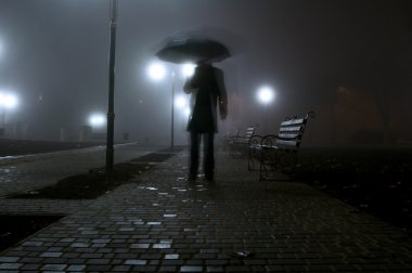 Man with umbrella in the night park