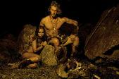 primitiver Mann und seine Frau sitzen in der Nähe des Feuers in der Höhle