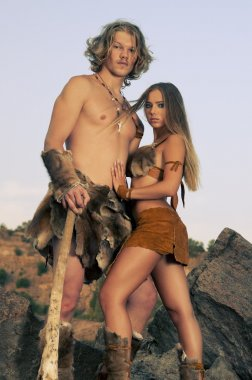 Primitive man standing near his woman.