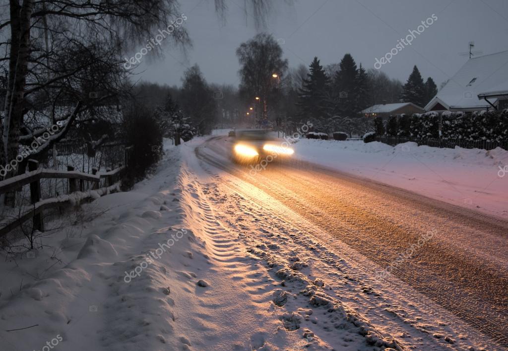 Car in suburb on winter night