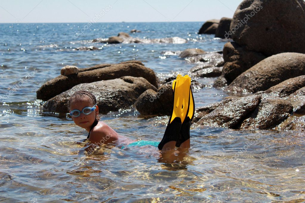 The girl on seacoast flounders about in water. In a mask and flippers