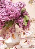 Fotografie Vintage teacup with spring flowers lilac