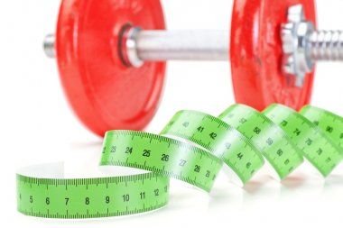Green measuring meter and dumbbells for fitness. On a white back